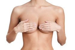 A topless woman holding her breasts