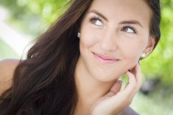 Young brunette woman touching her cheek and looking off to the right, as though enjoying the benefits of unaided vision thanks to custom LASIK surgery
