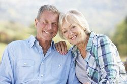 An older couple smiling outdoors