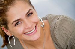 A woman with large earrings smiles