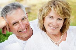 A middle-aged man and woman, both smiling to reveal their dental implant supported restorations