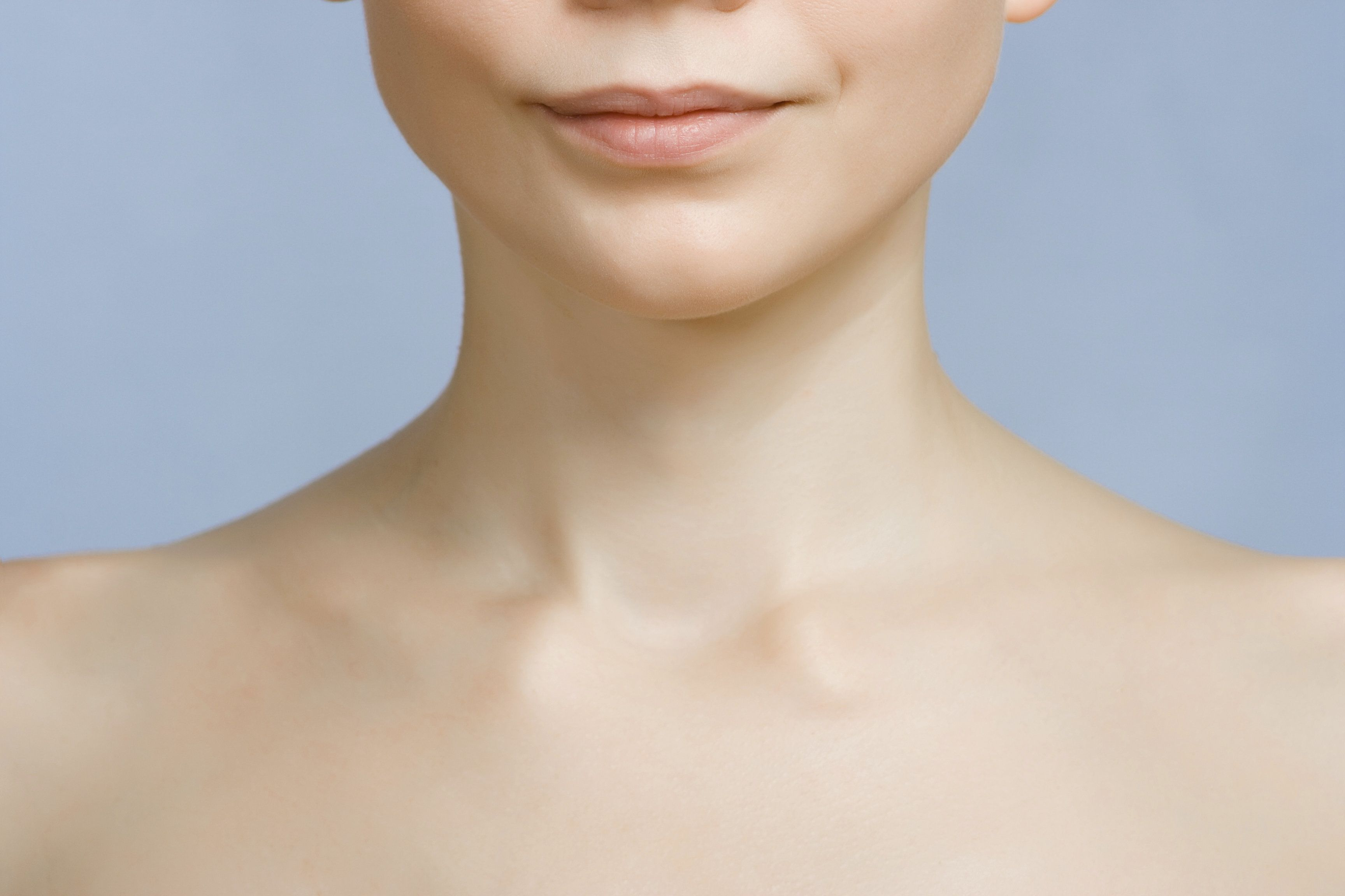 Up close photograph of a woman's neck and lower face in front of a blue background