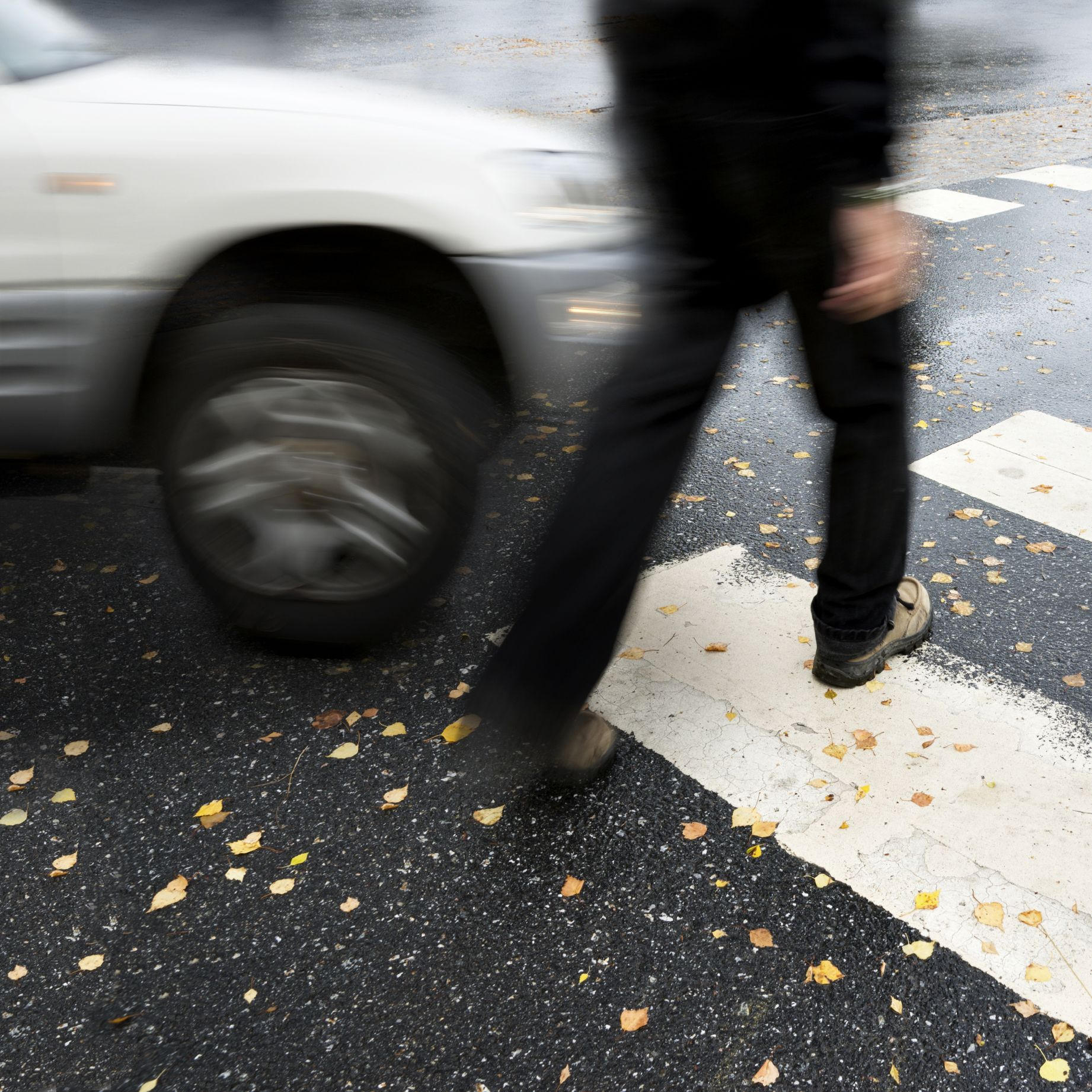 A pedestrian in a crosswalk about to be struck by an oncoming car