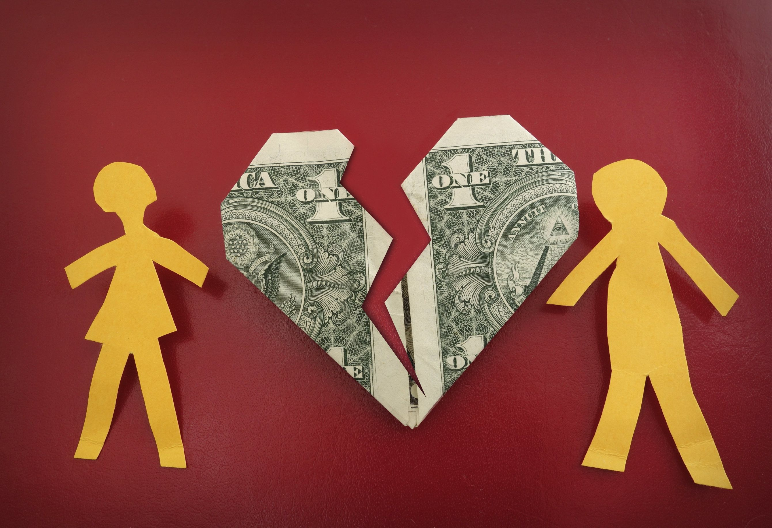 Cut out paper dolls and a dollar bill folded in the shape of a broken heart