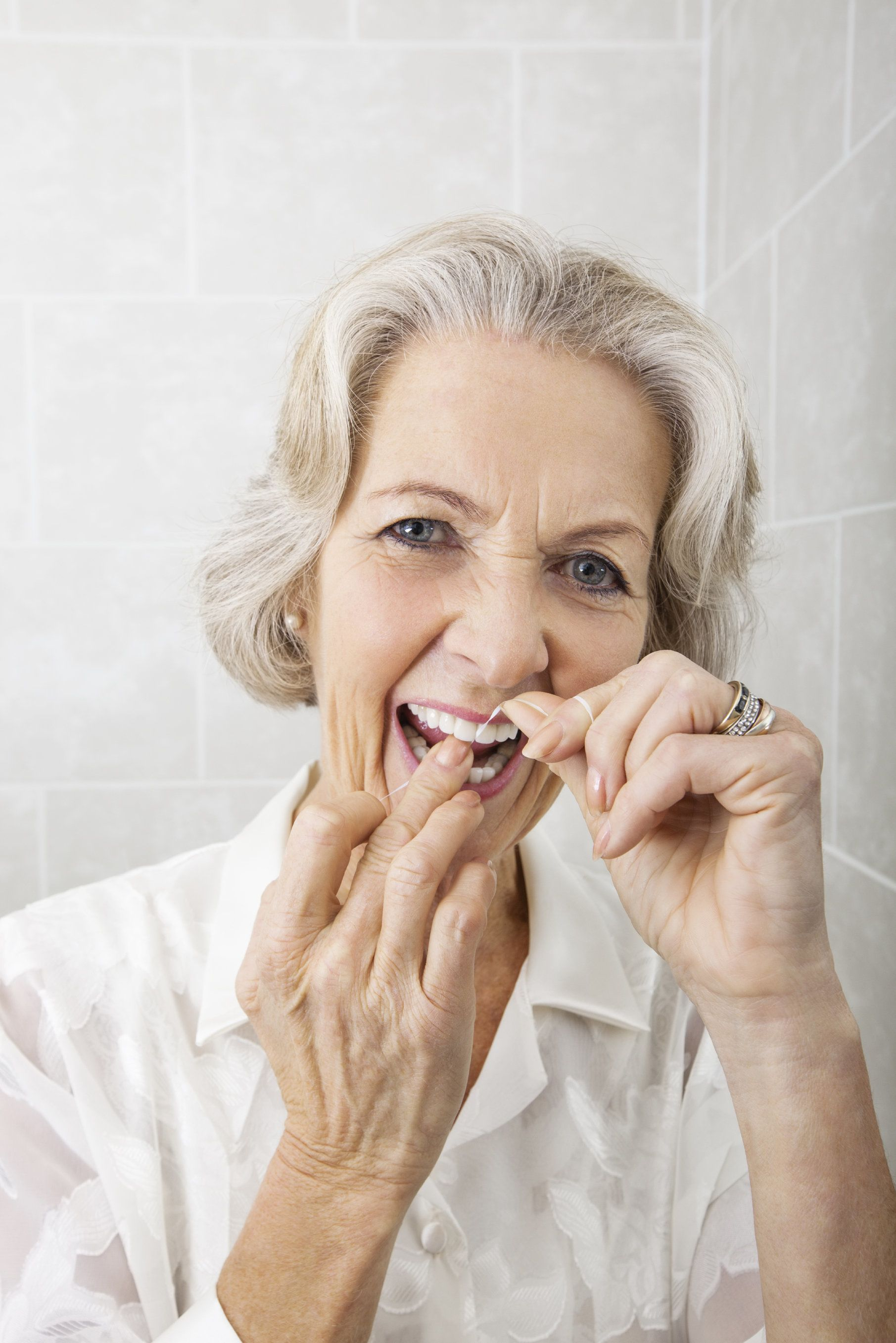 A senior woman flossing her teeth
