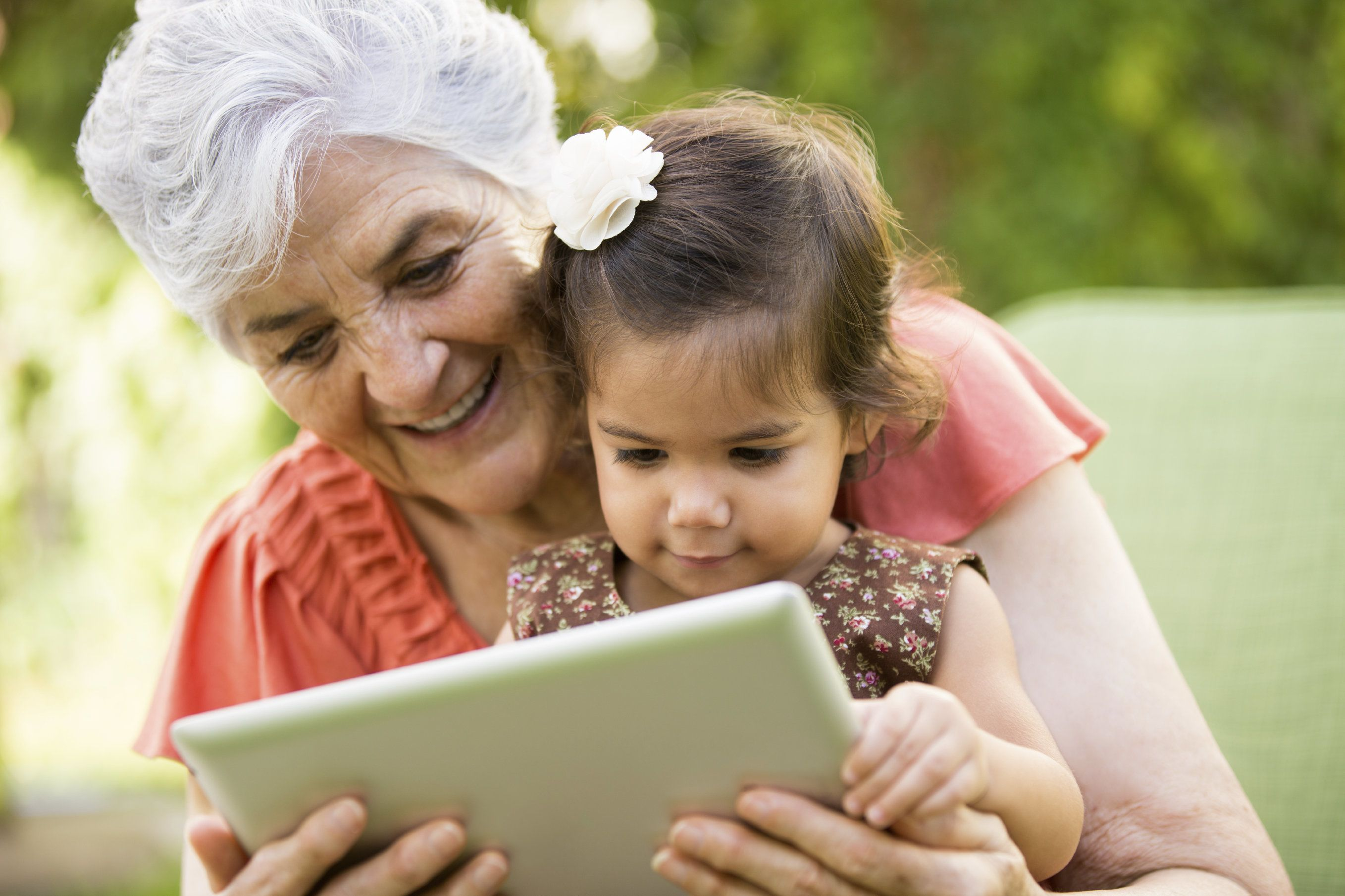 Older woman looking at tablet with toddler girl