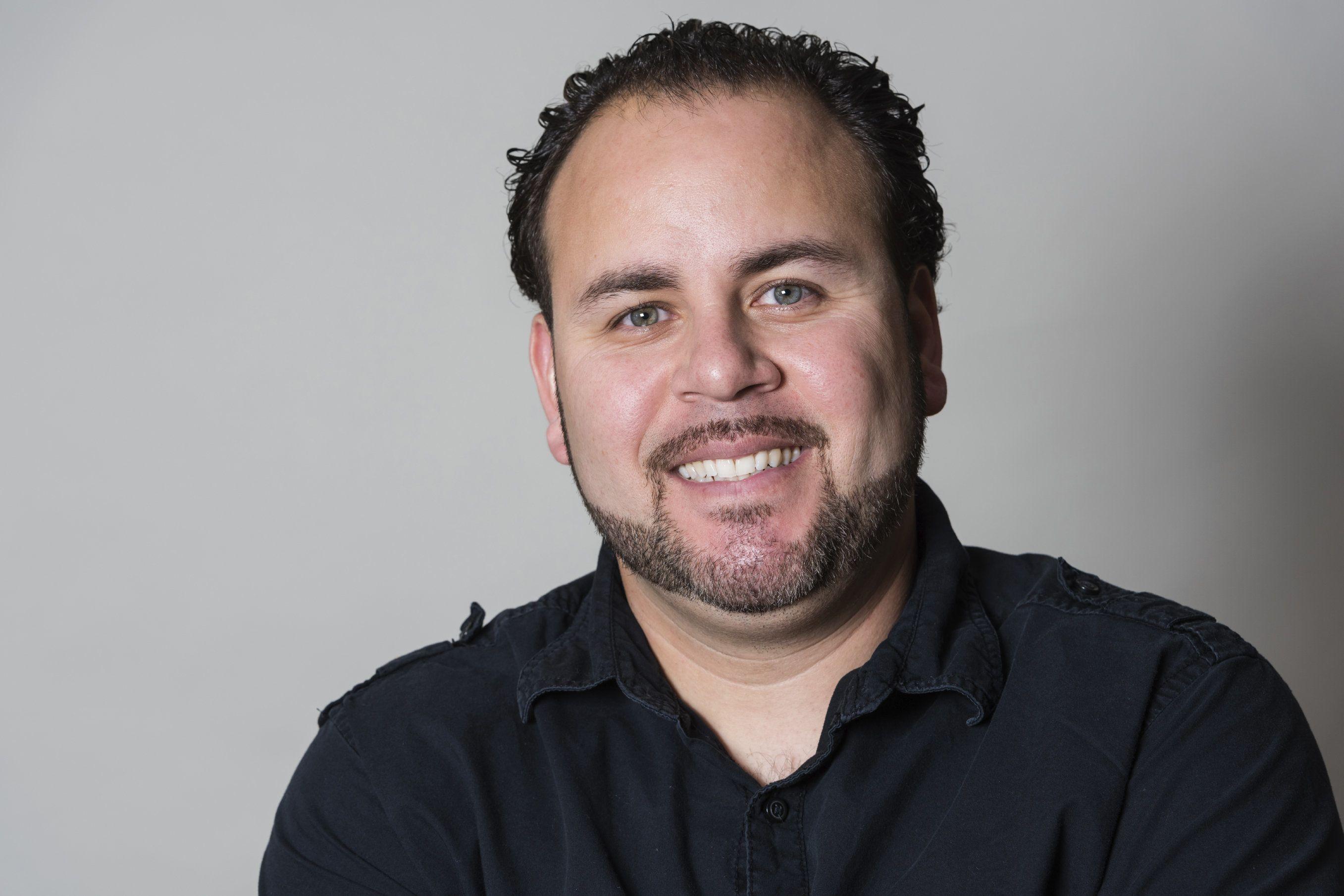 Man in dark blue shirt smiling.
