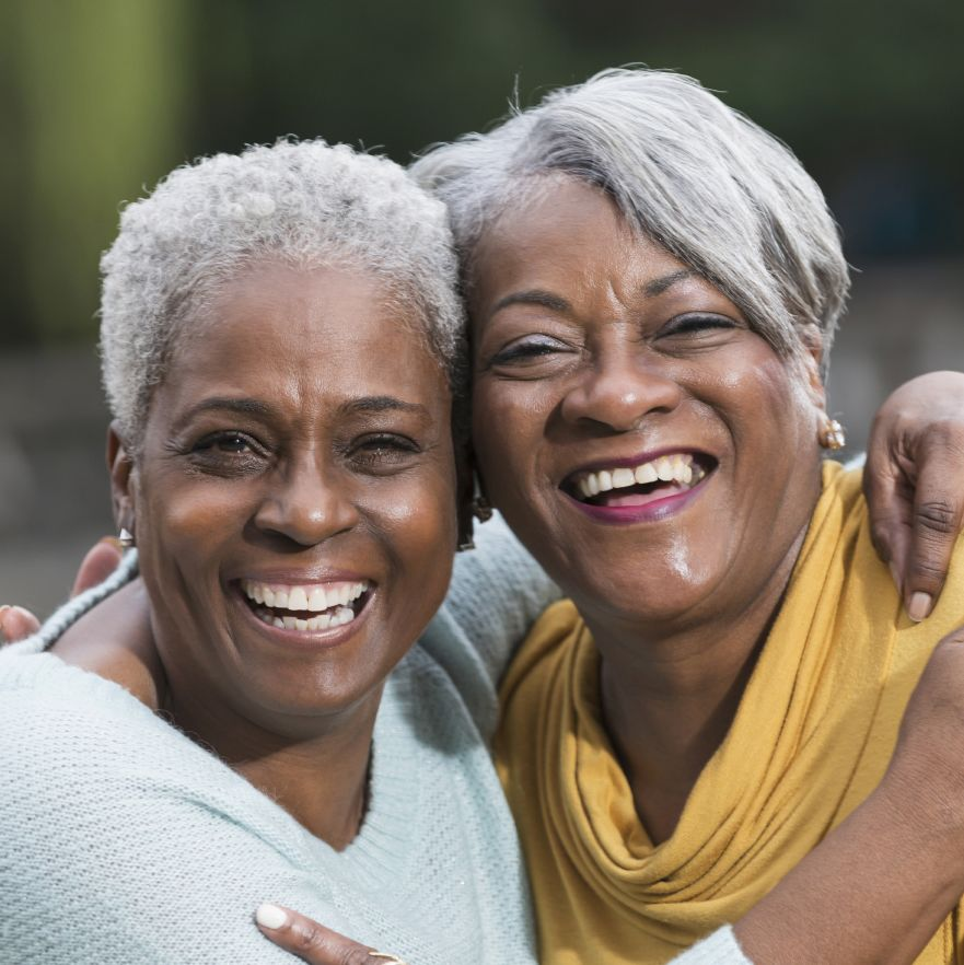Two older women with healthy looking smiles