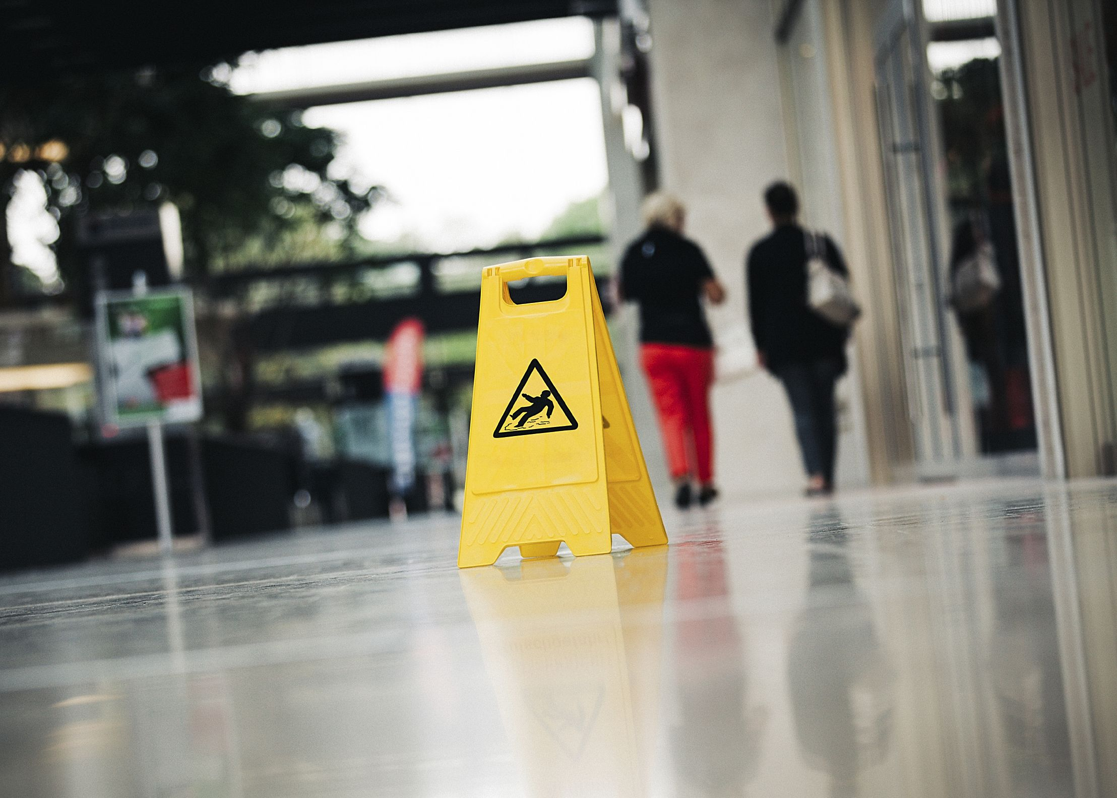 A sign indicating a wet floor and the possibility of a slip and fall accident