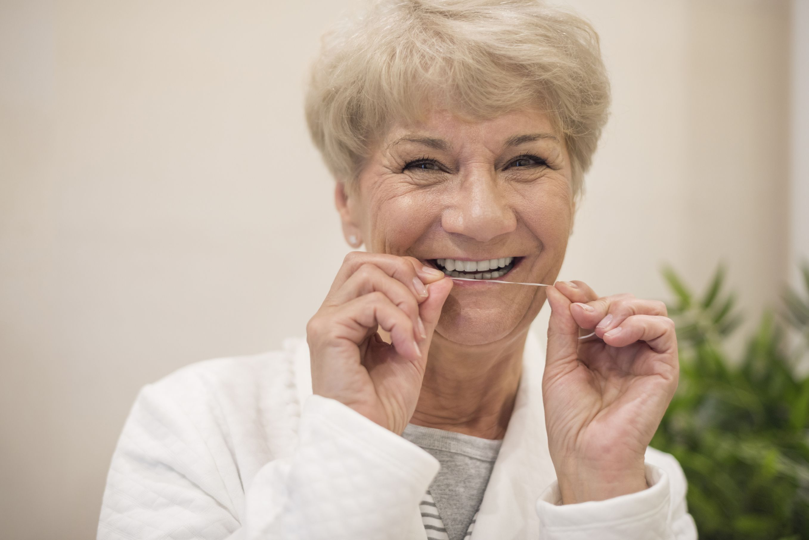 Portrait of smiling older woman flossing