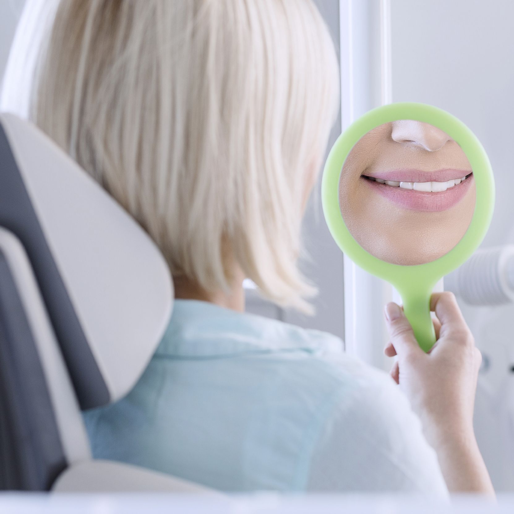 A woman smiling in a mirror, her teeth clean and healthy