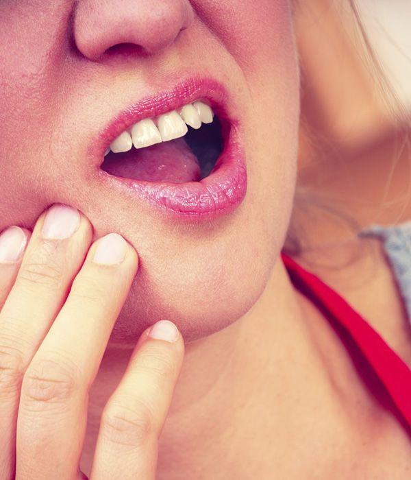 A woman clutching her jaw in pain due to tooth sensitivity while chewing