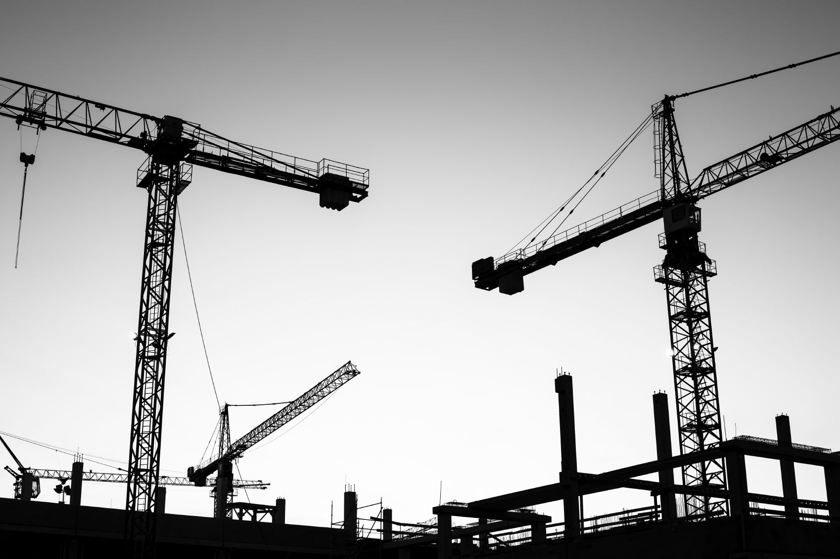 Black and white photo of two large cranes