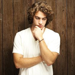 Pensive young man with curly brown hair