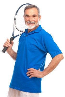 An elderly man with white hair and a white beard holding a tennis racket.