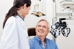 Smiling patient in exam chair speaking with ophthalmologist