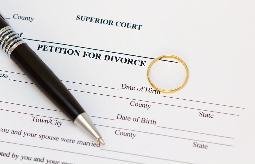 A wedding ring and a pen on top of divorce papers