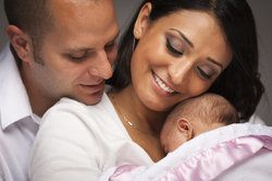 Couple embracing their newborn baby