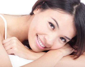 Attractive, smiling woman resting cheek on folded arms
