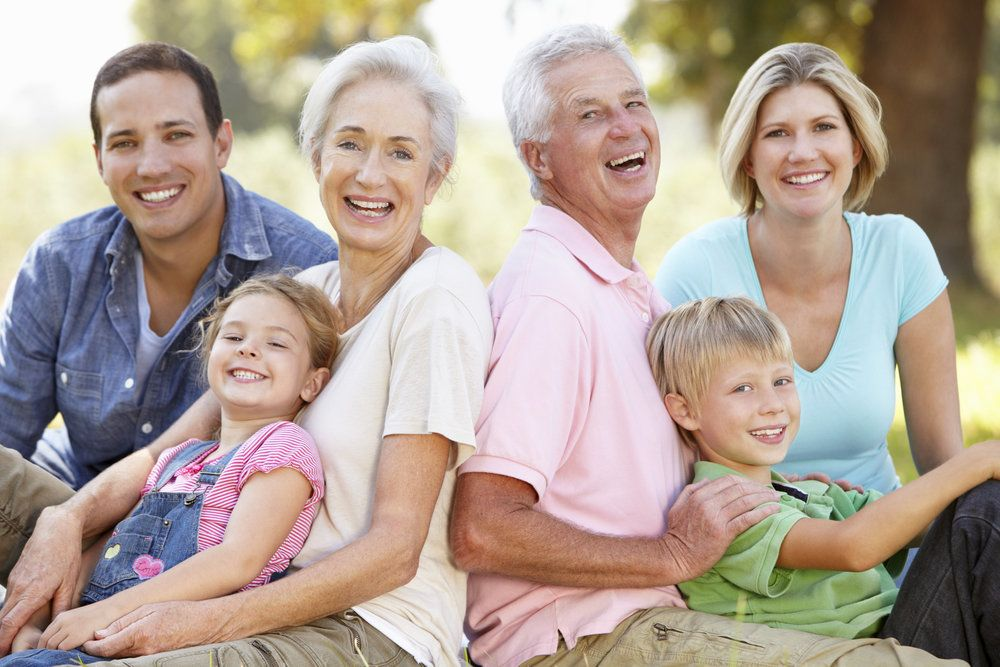 Two older adults smiling with their family