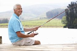 Man in blue shirt fishing off end of dock