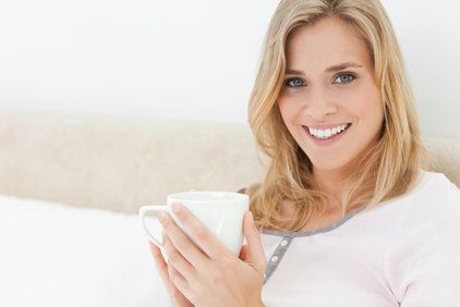 Smiling blond woman holding coffee cup