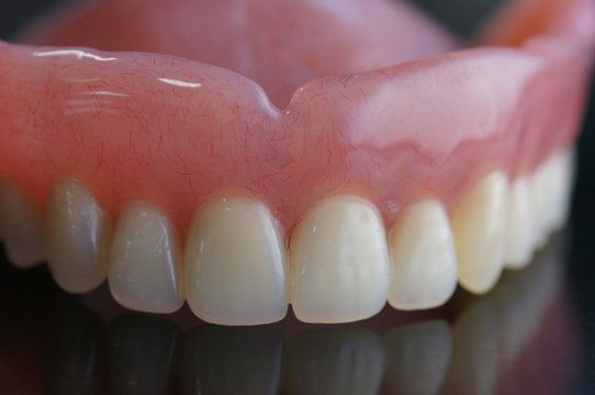 A full-arch denture sitting on a table