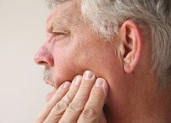 A middle-aged man holds his fingertips to his cheek as if in pain.