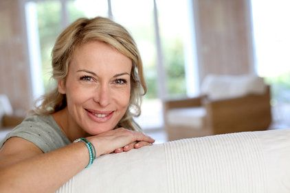A blonde woman smiles while peeking over her white couch.