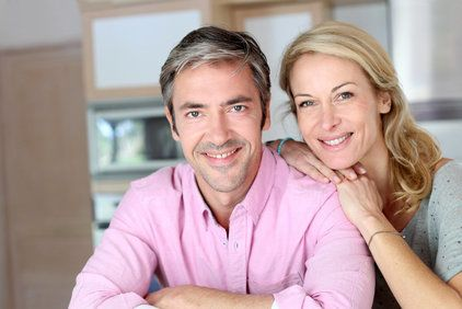 Smiling couple standing in kitchen with woman resting chin on husband's shoulder