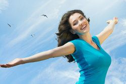 A woman outdoors and carefree with her arms outstretched