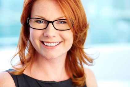 A pretty, young red-headed woman wearing glasses.