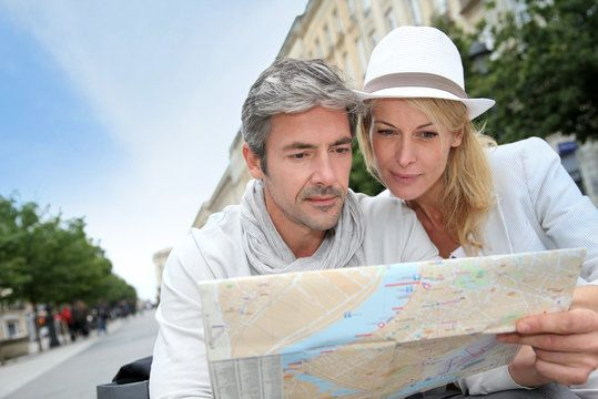 A couple looks at a map together with interest.