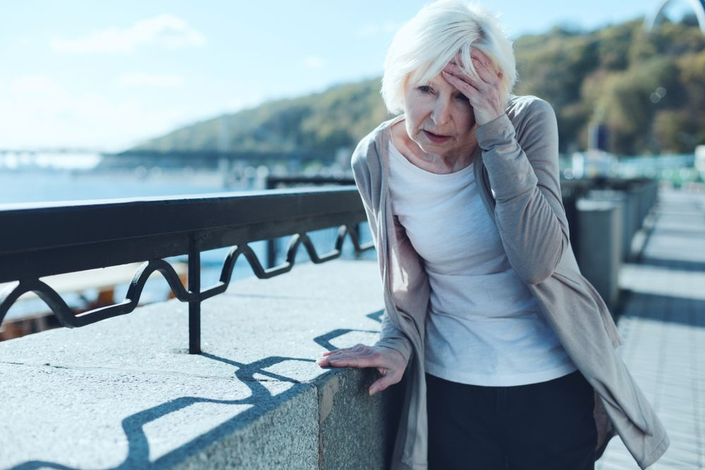 Older woman holding head in hands and leaning on railing