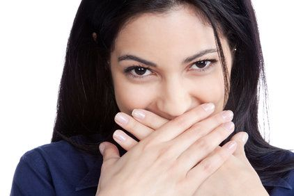 Woman smiling and covering her mouth