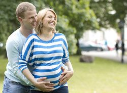 Man hugging laughing pregnant woman's stomach from behind
