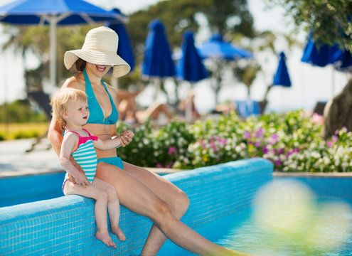 Woman in turquoise bikini relaxing at pool with small child