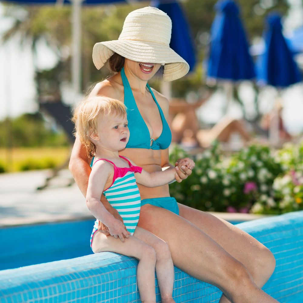 A woman with a flat stomach sitting with a child at a pool