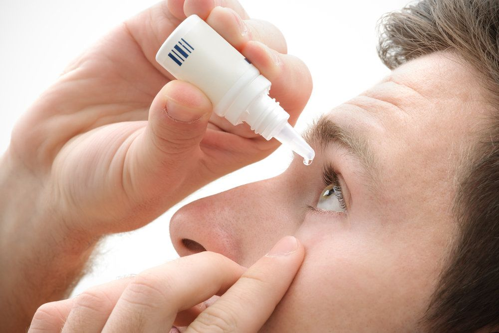 A man putting eyedrops in his eye.