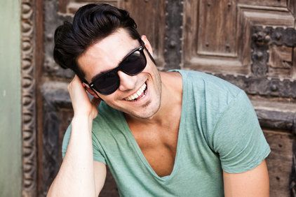 Smiling young man in sunglasses and v-neck shirt