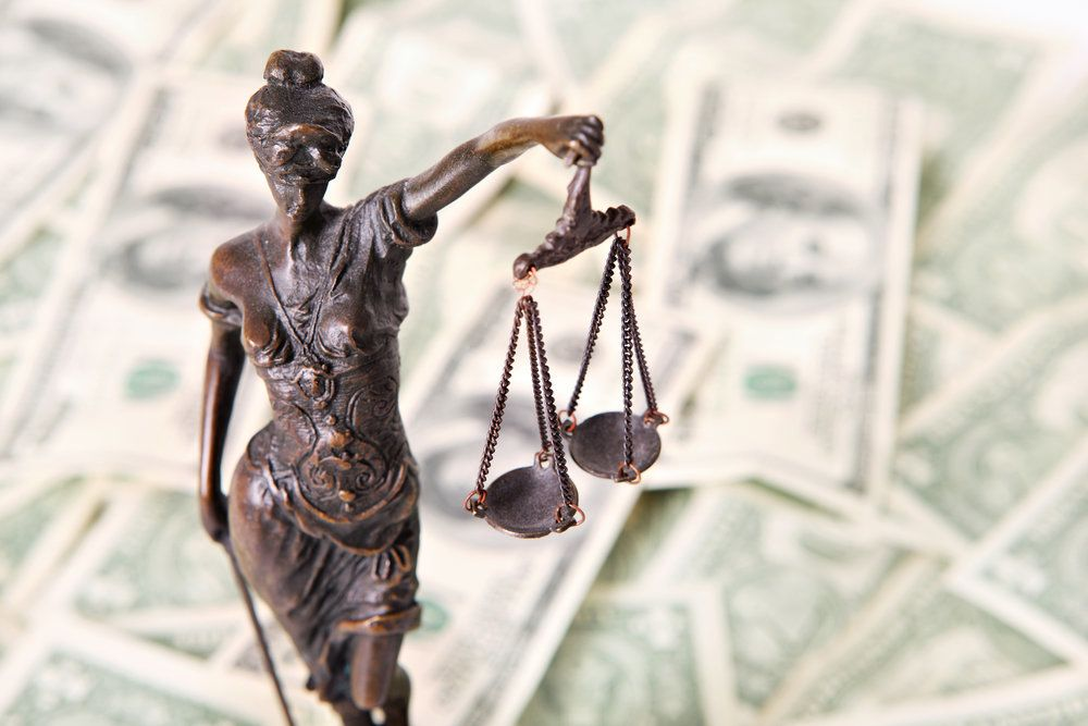 Lady Justice and her scales in front of money