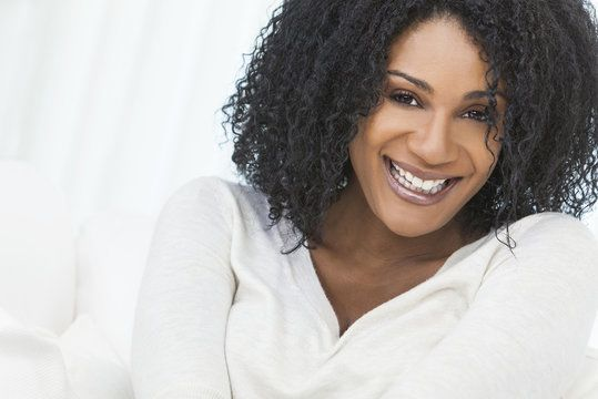 Laughing woman in white tunic shirt with curly, black hair