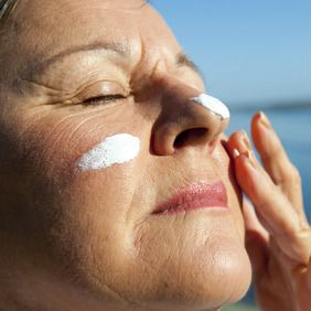 A close-up of a woman wearing white sun block on her nose