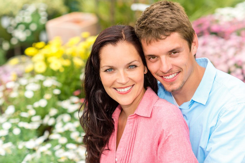 A young couple in an embrace, smiling contentedly after successful IVF treatment