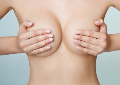 A woman holds her breasts in her hands