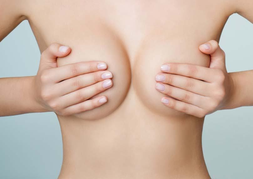 Woman tightly holding hands over her naked breasts