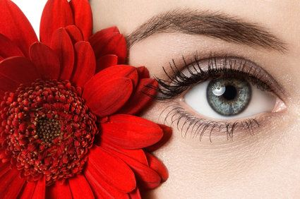 woman's eye next to red flower