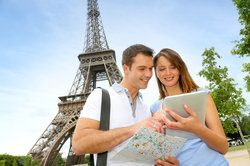 A couple uses a tablet near the Eiffel Tower