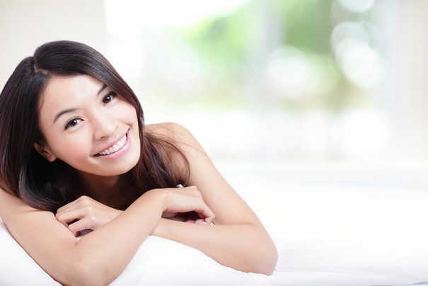 beautiful smiling dark haired woman laying on a pillow