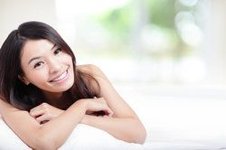 An attractive young woman with long black hair crosses her arms around a pillow and smiles